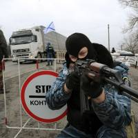 A man calling himself a member of Ukraine's disbanded Berkut riot police force aims a Kalashnikov rifle at a checkpoint on a highway that connects the Black Sea Crimean Peninsula to mainland Ukraine near the city of Armyansk on Friday. Behind him are the Russian national (left) and naval flags. | AFP-JIJI