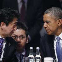 U.S. President Barack Obama talks to Prime Minister Shinzo Abe at the opening session of the Nuclear Security Summit in The Hague on Monday. | AP