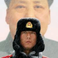 A paramilitary policeman stands guard in front of the giant portrait of late Chinese Communist Party leader Mao Zedong at the main entrance to the Forbidden City in Beijing on Feb. 7. | REUTERS