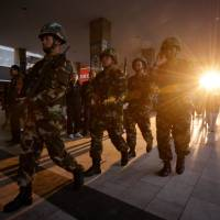 Paramilitary police patrol outside the scene of a deadly attack that left 33 dead at the Kunming train station, in China's Yunnan Province, on Monday. | AFP-JIJI
