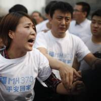 A relative of passengers who disappeared with Malaysia Airlines Flight MH370 yells at security personnel during a protest outside the Malaysian Embassy in Beijing on Tuesday. | AFP-JIJI