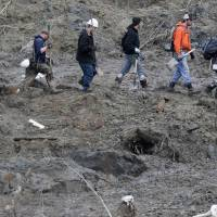 Rescue workers search for the victims of a massive mudslide near Oso, Washington state, as efforts continued Wednesday to locate missing residents and the death toll rose to 24. | REUTERS