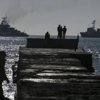 People watch Russian ships blockading the exit of Donuzlav Bay in Crimea, where three Ukrainian Navy ships have refused to surrender to Russian forces, on Sunday. | REUTERS
