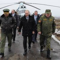 Russian President Vladimir Putin (center), Defense Minister Sergei Shoigu (left) and Anatoly Sidorov, the commander of the Western Military District, walk upon arrival to watch military exercise near St. Petersburg, Russia, on Monday. | AP
