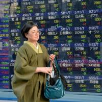 A woman walks past a stock price board in Tokyo on Monday. According to the Metropolitan Police Department, fewer than 40 percent of residents and commuters in the capital have taken specific measures to prepare for the possibility of a huge earthquake striking the metropolis. | AFP-JIJI