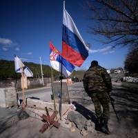 The national flags of Russia (right) and Serbia (center) and a Russian navy flag adorn a check point on the road from Simferopol to Sevastopol in the Crimean region of Ukraine on Thursday. | AFP-JIJI
