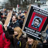 Ukrainians and Poles protest in front of the Russian Embassy in Warsaw over Russian military action in the Crimean Peninsula on Sunday. | AFP-JIJI