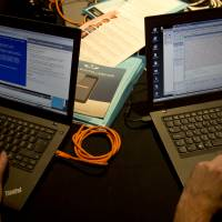 Computer aficionados work on laptops during a mock cyberattack scenario in London on Friday. The U.S. government announced the same day that it was giving up its key role overseeing the Internet's technical operations, handing over those functions to 'the global multi-stakeholder community.' | AP