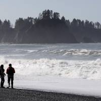 A couple walk along the coast at Olympic National Park near Forks, Washington, on Tuesday, the third anniversary of the magnitude-9 earthquake and tsunami that sparked the Fukushima No. 1 nuclear power plant disaster. Scientists predict low levels of radiation from Fukushima will reach waters off the Pacific Northwest next month. | REUTERS