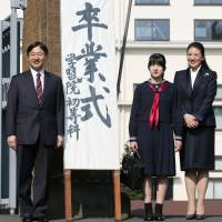 Princess Aiko, flanked by her parents, Crown Prince Naruhito and Princess Masako, stands at the gate to Gakushuin Primary School in Tokyo before attending her graduation ceremony Tuesday. | KYODO