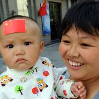 A Chinese baby with a national flag sticker on his forehead watches as people attend an anti-Japanese protest over the Senkaku Islands issue outside the Japanese Embassy in Beijing in September 2012. According to Chinese authorities, more than 260 unwanted children, most of them babies, have been abandoned at a Chinese 'safe haven' in Guangzhou, Guangdong province, in just over six weeks. | AFP-JIJI