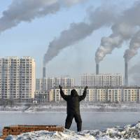 A man exercises in the morning as he faces chimneys emitting smoke behind buildings across the Songhua River in Jilin, China, in February 2013. | REUTERS