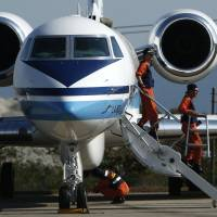Japan Coast Guard personnel prepare their Gulfstream V jet, customized for search and rescue operations, before joining the hunt for missing Malaysia Airlines flight MH370 Saturday. | REUTERS