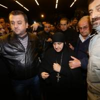 Kidnapped nuns formerly held by Syrian rebels arrive at Jdeidet Yabus on the Syrian side of the border with Lebanon on Monday, following a rare prisoner exchange with Syrian authorities that also saw dozens of women freed from government prisons. | AFP-JIJI