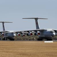 Two Chinese Air Force Ilyushin Il-76 aircraft, which joined the search for Malaysian Airlines flight MH370, sit on the runway at an Australian air base in Bullsbrook, near Perth, on Sunday. | REUTERS