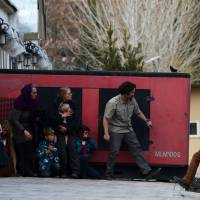 Foreigners take refuge behind a generator after they were evacuated from an American charity and a nearby day care center during an attack by Taliban gunmen Friday in Kabul. | AFP-JIJI