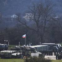 A Russian flag flies over Russian troops as they gather at a former Ukrainian military base in Perevalne, outside Simferopol in Crimea, on Thursday. | AP