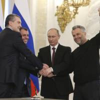 Russia's President Vladimir Putin (second from right), Crimean Prime Minister Sergei Aksyonov (left), parliamentary Speaker Vladimir Konstantinov (second left) and Sevastopol Mayor Alexei Chaliy shake hands after a signing ceremony for the region's secession to Russia at the Kremlin in Moscow on Monday. | REUTERS