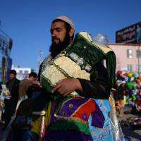 An Afghan vendor sells clothes in Mazar-i-Sharif on Sunday. Afghanistan's economy has improved significantly since the fall of the Taliban in 2001, but despite international assistance the country needs to overcome challenges, including low revenue collection and job creation, corruption, weak government capacity and poor public infrastructure. | AFP-JIJI