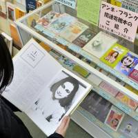 A woman reads donated books relating to Anne Frank at a public library in Suginami Ward, Tokyo, on Saturday. | AFP-JIJI