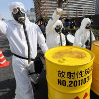 People in protective suits and masks shout slogans next to mock drums of nuclear waste from the Fukushima No. 1 power plant during a march denouncing nuclear power in Tokyo on Sunday. | AFP-JIJI
