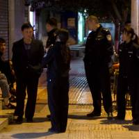 Police officers question two Uighur men (left) as a Han Chinese man walks past them in the Chinese city of Kunming, which saw a vicious slashing spree Saturday that killed 29 people. | AP
