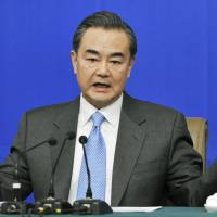 Chinese Foreign Minister Wang Yi gestures during a news conference Saturday in Beijing on the sidelines of the annual session of the National People's Congress, China's legislature. | KYODO