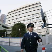 Policemen guard the Tokyo headquarters of the General Association of Korean Residents in Japan (Chongryon) on Monday. The pro-Pyongyang entity will finally have to vacate the building if its sale to real estate developer Marunaka Holdings Co. receives court approval. | KYODO