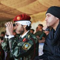 Saadi Gadhafi, center, and Hannibal Gadhafi, right, sons of Libyan leader Moammar Gadhafi, watch a 2011 military exercise by the elite unit commanded by their brother, Khamis, in Zlitan, 140 km southeast of Tripoli, Libya. Libya says Niger has extradited Saadi to Libya. | AP