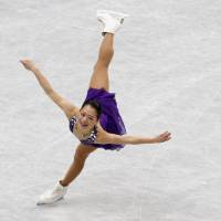 Purple prose: Akiko Suzuki performs her short-program routine at the world championships on Thursday. | REUTERS