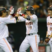 Exciting start: Yasuyuki Kataoka (center) is congratulated by Giants teammates Hayato Sakamoto and Tomoyuki Sugano after hitting a three-run home run in the fifth inning against the Tigers on Friday at Tokyo Dome. Yomiuri defeated Hanshin 12-4. | KYODO