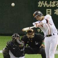 Century mark: Giants star Hayato Sakamoto hits his 100th career home run in the fourth inning on Opening Night. | KYODO