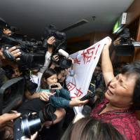 A Chinese relative of passengers aboard the missing Malaysia Airlines Flight MH370 cries as she holds a banner in front of journalists reading 'We are against the Malaysian government for hiding the truth and delaying the rescue. Release our families unconditionally!' at a hotel in Sepang, Malaysia, on Wednesday. | AP