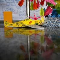 A toy plane and cards with personalized messages dedicated to people on missing Malaysia Airlines Flight MH370 are placed at the viewing gallery of Kuala Lumpur International Airport on Saturday. | AP