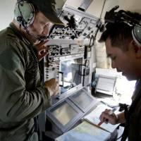 Crew members on a Royal Australian Air Force AP-3C Orion aircraft scrutinize navigation maps as they search for missing Malaysian Airlines Flight MH370 over the southern Indian Ocean on Thursday. | AP