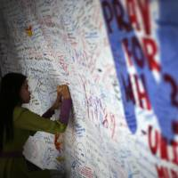 A woman writes a message of hope on a board dedicated to the 239 people on board the missing Malaysia Airlines jetliner at Kuala Lumpur International Airport on Saturday. | AP