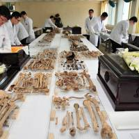 South Korean soldiers in white lab coats wrap the remains of Chinese war dead before placing them in coffins at a military base in Paju, north of Seoul, on Monday. The remains of more than 400 Chinese soldiers killed during the 1950-1953 Korean War will return home from South Korea for permanent burial. | AP