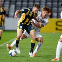 Standard procedure: Central Coast Mariners player Mitchell Duke is tackled by Sanfrecce Hiroshima's Park Hyung-jin in their AFC Champions League match in Gosford, Australia, on Tuesday. | AFP-JIJI