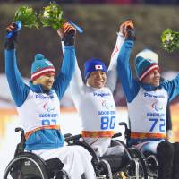 Recognition time: Gold medalist Takeshi Suzuki (center) is joined by Austrian teammates Philipp Bonadimann and Roman Rabl, the silver and gold medalists, respectively after the men's sit-ski slalom at the Sochi Paralympics on Thursday. | KYODO