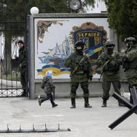 A boy runs by as Ukrainian soldiers look on from behind gates as Russian soldiers guard the gate of an infantry base in Perevalne, Ukraine, on Tuesday. | AP