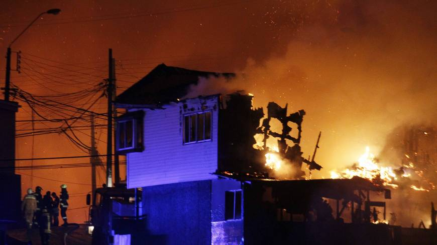 A group of firefighters stand next to burning homes as a forest fire rages Sunday toward urban areas in the city of Valparaiso, Chile.