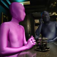 Hokkyku Nigo (left) sits with a man at a bar in Tokyo. She is part of a small subset in Japan with a fetish for wearing outfits called 'zentai' —an abbreviation of 'zenshintaitsu', which means 'full body suit. Its fans say they are seeking liberation through the complete sublimation of the physical self.   | AFP-JIJI