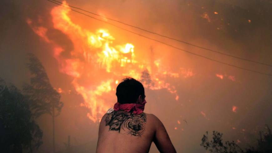 A man watches houses going up in in flames during a fire in Valparaiso, Chile, Sunday.