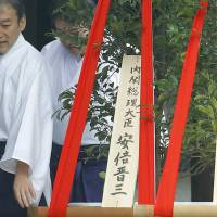 Wooden plaques bearing the names 'Prime Minister Shinzo Abe' (left) and 'Upper House President Masaaki Yamazaki' are placed together with their 'masakaki' ceremonial tree offerings at Yasukuni Shrine in Tokyo on Monday. | KYODO