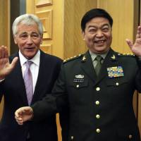 U.S. Defense Secretary Chuck Hagel and his Chinese counterpart, Chang Wanquan, wave to members of the media prior to their meeting in Beijing on Tuesday. | REUTERS