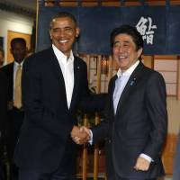 U.S. President Barack Obama is welcomed to the restaurant Sukiyabashi Jiro by Prime Minister Shinzo Abe in Tokyo on Wednesday. | REUTERS