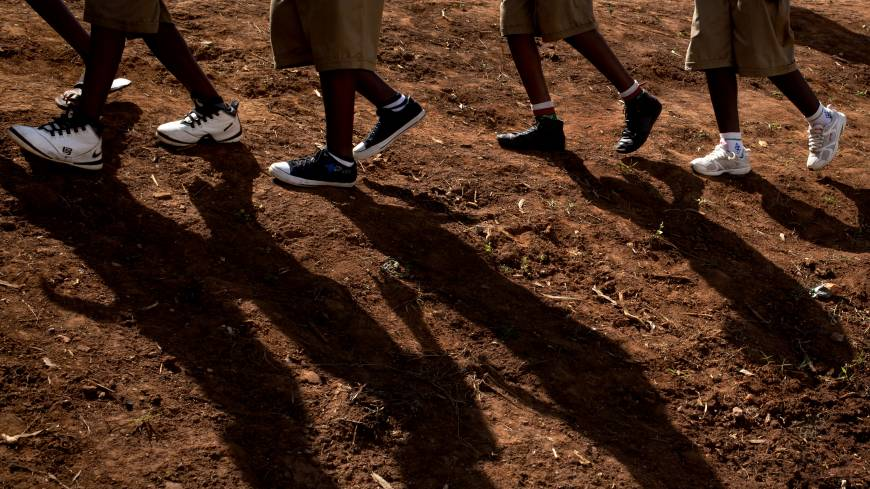 Rwandan children walk to a torch ceremony symbolizing remembrance and to hear genocide victims recount their memories at the Petit Seminaire school in Ndera, east of the capital, Kigali, on Thursday.
