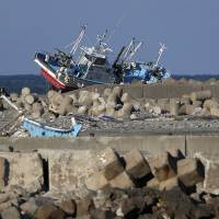 A fishing boat swept onto a breakwater by the tsunami sits abandoned in Namie, Fukushima Prefecture, on March 10. | BLOOMBERG
