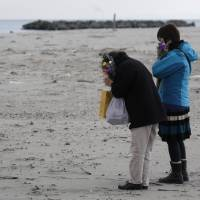 People pray on the third anniversary of the Great East Japan Earthquake and tsunami last month at a coastal stretch damaged by the disaster in Sendai. | BLOOMBERG