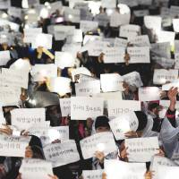 Students at Danwon High School in Ansan, South Korea, hold messages for fellow students who were on the capsized passenger ferry Sewol. About 270 of the 475 passengers and crew members were still missing Friday, and 28 were confirmed dead. | AFP-JIJI